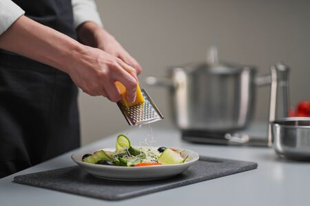 A female chef in a white uniform and a black apron in the restaurant kitchen. Cooking a salad of vegetables. The cook rubs the parmesan cheese on a small grater. Imagens