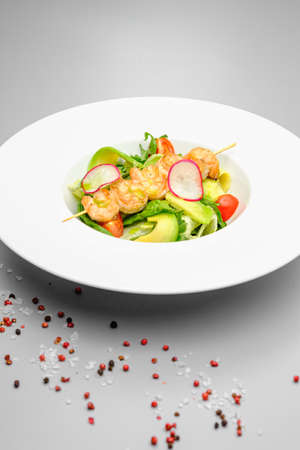 Grilled shrimp on a skewer with vegetables on a white plate on a gray background. Food in the restaurant.