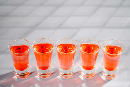 Red alcoholic shot drinks in glasses in a row on the bar count. Restaurant menu.