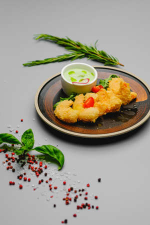 Shrimp fries in breadcrumbs on a gray background decorated with basil, sea salt and pepper. Snacks on the dinner restaurant menu. Stock fotó