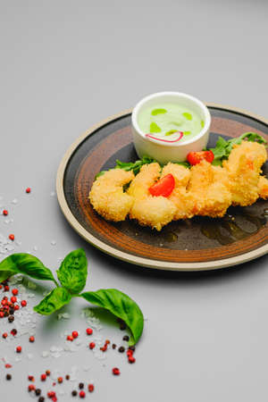 Shrimp fries in breadcrumbs on a gray background decorated with basil, sea salt and pepper. Snacks on the dinner restaurant menu. Archivio Fotografico