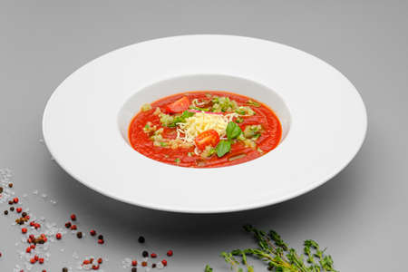 Tomato soup minestrone with cheese in a white plate on a gray background. The food is on the restaurant menu. Stock fotó