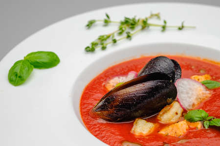 Tomato soup mashed with seafood mussels in a white plate on a gray background. Lunch at the restaurant. Stock fotó