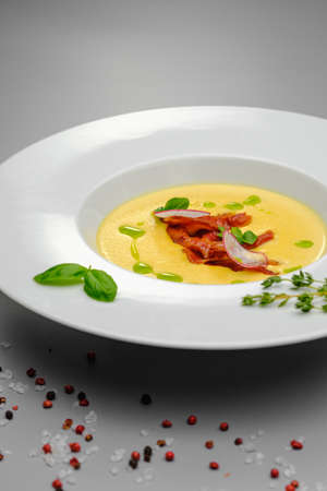 Corn cream soup with smoked meat in a white plate decorated with basil, on a gray background. The first course on the restaurant menu. Dinner.