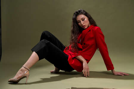 A sensual young woman in a red jacket, culottes and shoes with wet long black hair poses against a green background in the studio. Fashion and beat photography.