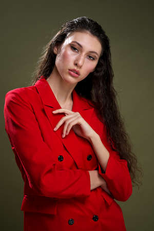 A sensual young woman portrait in a red jacket, with wet long black hair poses against a green background in the studio. Fashion and beat photography. Zdjęcie Seryjne
