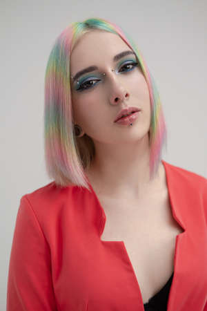 Portrait of a young beautiful informal blonde girl with dyed hair. Red jacket suit on the naked body. Studio photoshoot on a white background. Creative makeup.