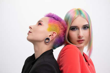 Young lesbian woman couple with vivd colored short hair and jackets posing on white background. Piercing on the face, tunnels in the ears. The concept of same-sex wedding.