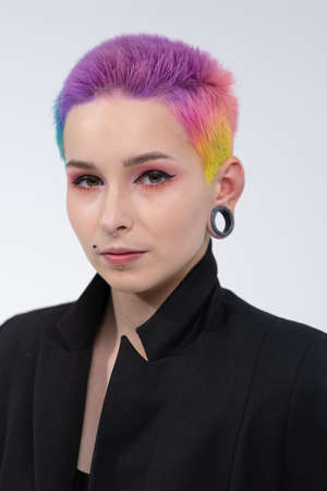 A young beautiful girl with short colored hair. Spread bright coloring and creative make-up. Piercing on the face. A black jacket. Photo shoot on a white background. Banco de Imagens
