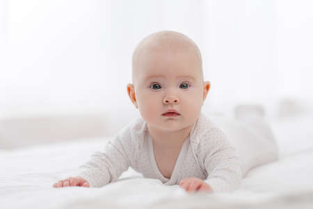 Portrait of a cute beautiful baby with gray eyes in white pajamas on the bed against the window. Light home interior. Banco de Imagens