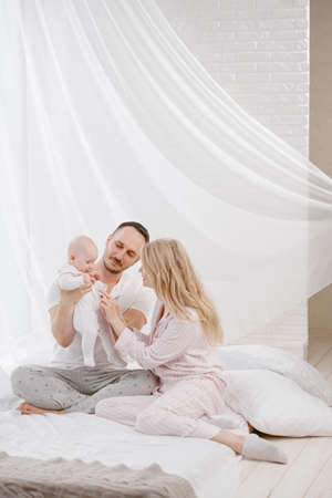 A young Caucasian family with a newborn baby daughter in the bedroom. White light home interior. They laugh and hug. Banco de Imagens