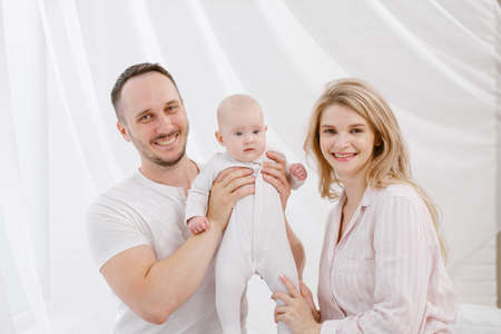 A young Caucasian family with a newborn baby daughter in the bedroom. White light home interior. They laugh and hug.