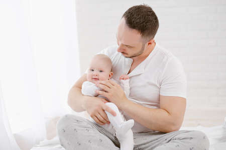 A young father holds a newborn baby daughter. White background, home interior.