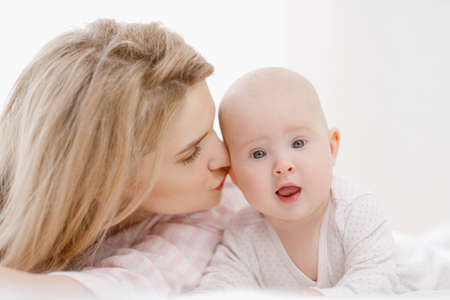 Young beautiful Caucasian blonde mom lies on the bed with her baby daughter. White light home interior. Love and care.