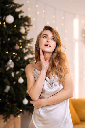 Portrait of a young pretty and dreamy blonde woman with a silver dress against the backdrop of the Christmas tree. Cozy home interior.