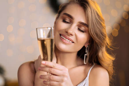 A young beautiful blonde woman in a silver cocktail dress holds a glass of champagne. Smiling and posing against the backdrop of a Christmas tree. Makes a wish and celebrates. Фото со стока