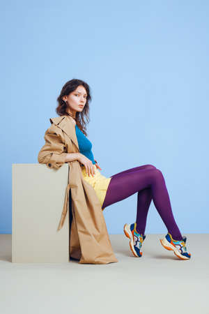 A young fashion girl in a beige trench, yellow short skirt, purple tights and sunglasses on minimal blue and biege background with cube.