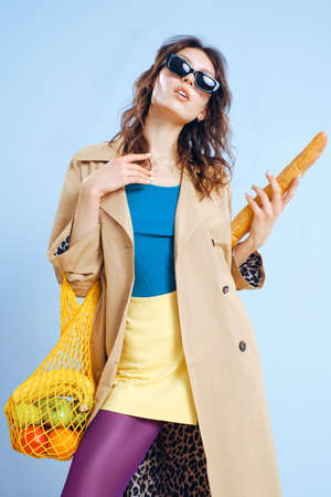 A young fashion girl in a beige trench, yellow short skirt, purple tights and sunglasses holds a mesh reusable eco bag with food.