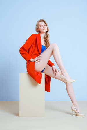 Young fashionable blonde Caucasian woman in a blue merged swimsuit, beige high-heeled shoes and red trench. Beautiful long legs, light soft and smooth skin. Minimalistic blue background.