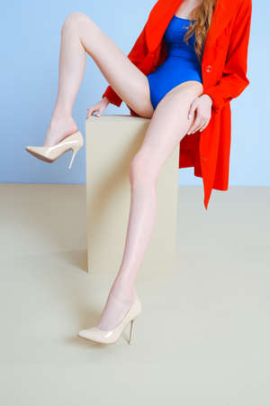 Close-up of beautiful long white womens legs in beige shoes. A woman on a minimalist beige and blue background. Blue merged swimsuit and red trench. Фото со стока
