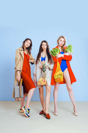 Three young fashionable females housewives in red and blue swimsuits and trench coats on naked body. Shopper strip bags with food in hands. Shopping, purchasing and consumerism. Beautiful long legs.