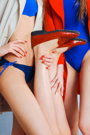 Red loafers close up on beautiful legs. The concept of advertising shoes. Smooth skin, depilation. Red and blue. The hands and feet of three beautiful girls. Фото со стока