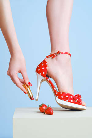 Lipstick in hand and red high-heeled shoes close-up on a blue background. Advertising cosmetics and shoes.