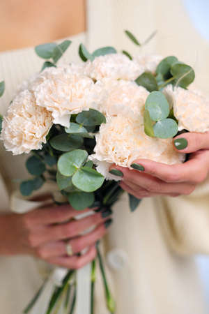 A young woman holds a delicate bouquet of cream carnations.
