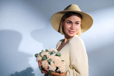 A young beautiful blonde caucasian woman with a short haircut in a beige suit and hat with bouquet of white flowers on blue background. Beauty portrait. The girl smiles, clean skin and white teeth.