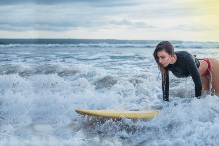 action of young woman try to step standing on the surfboard in the med of the ocean.