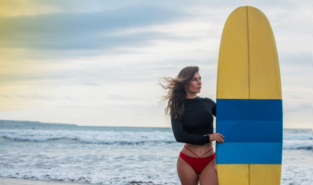 Surfer woman going surfing standing with blue-yellow surfboard on Waikiki Beach. 版權商用圖片