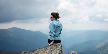 Gilr sitting on a high mountain. Freedom, traveling, hiking and trekking concept.