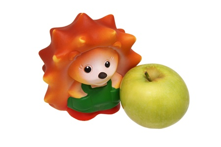 Rubber toy hedgehog and green apple  Close-up Stock Photo - 17935661