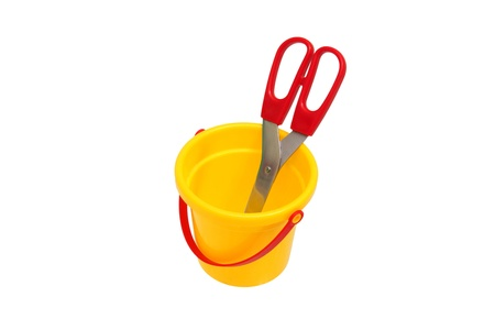 scissors with red handle in the children yellow plastic bucket                                photo