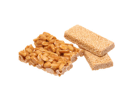 Peanut brittle with sesame seeds and peanuts. Isolated on white.