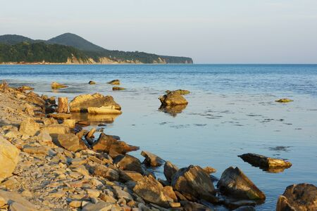 Stony coast and mountains in the background. Landscape.
