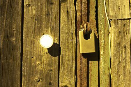 Padlock on an old wooden door. Close-up.