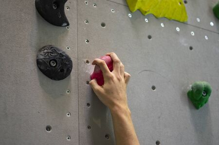 Free climbing in a climbing gym detail hand food on a climbing wall 스톡 콘텐츠