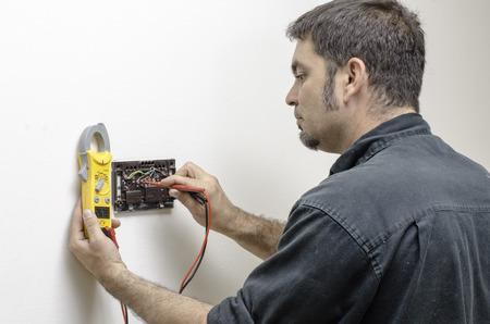 HVAC technician testing voltage on a mercury thermostat