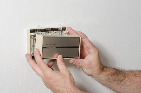 thermostat: Hands removing and older style thermostat cover
