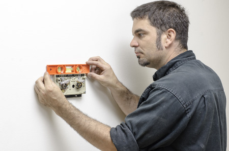 home appliances: HVAC technican making sure an old mercury thermostat is level