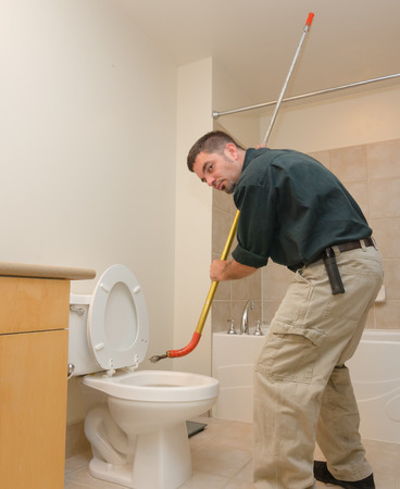 clog: Plumber unclogging a toilet with manual auger