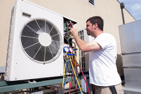 air: HVAC technician working on a mini-split condensing unit Stock Photo
