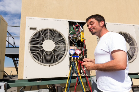 cooling system: HVAC technician working on a mini-split condensing rooftop unit