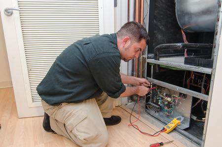 HVAC-technicus werkt aan een residentiële warmtepomp Stockfoto