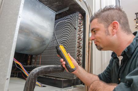Een HVAC-technicus op zoek naar een koelmiddel lek op een verdamper.