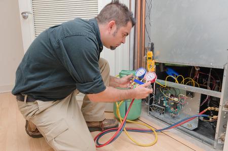 electricista: HVAC t�cnico de la carga de una bomba de calor con refrigerante Foto de archivo