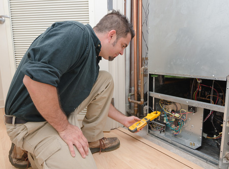 air: HVAC technician using a meter to check heat pump amperage Stock Photo