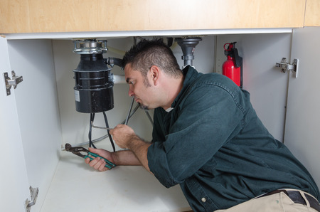 garbage disposal: A plumber laying under a house hold sink working on a garbage disposal.