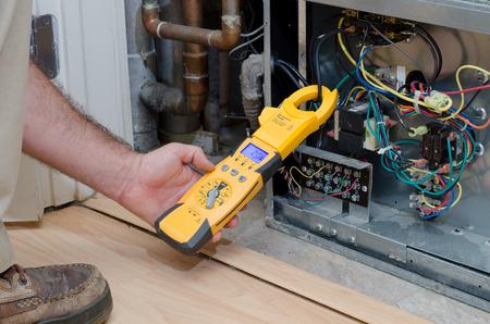 住宅のヒートポンプのアンペア数をチェックする空調技術者